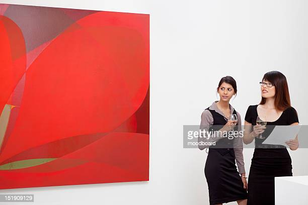 Young women looking at wall painting in art gallery