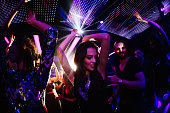 Young women dancing happily with her friends in a nigh club party with disco lights