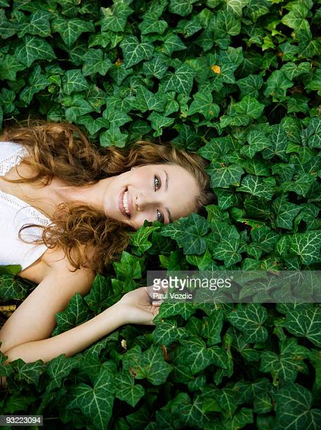 Young women lying in ivy