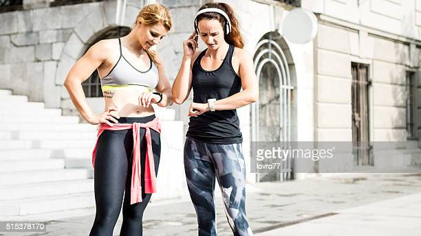 Young women measuring heart rate after running