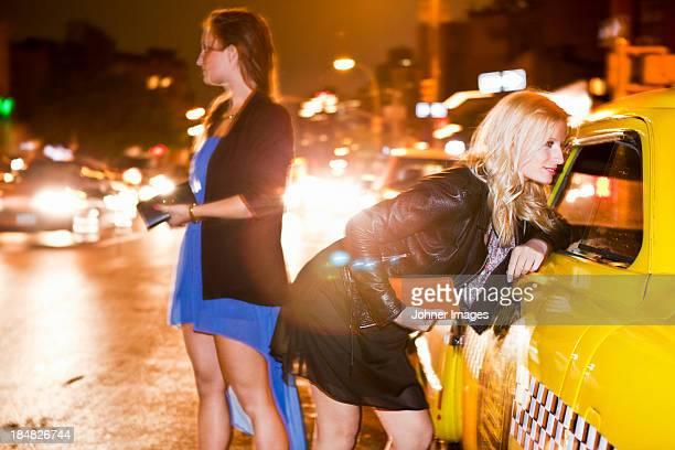 Young women near taxi