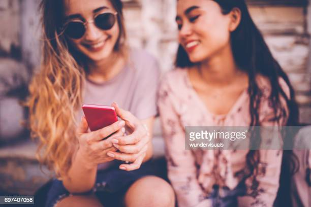 Young women on a city break social-networking on a smartphone