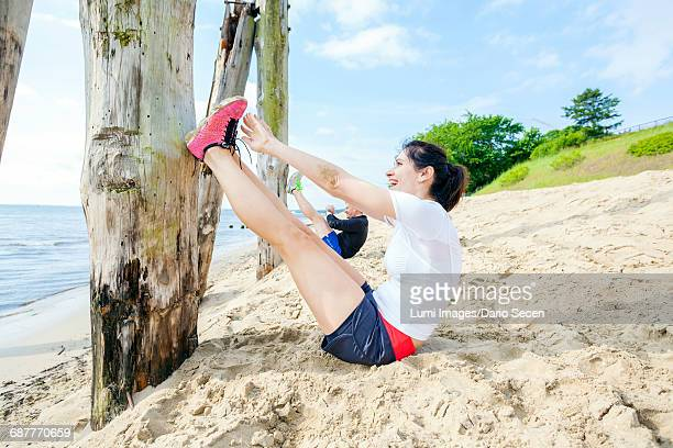 Young women on beach doing sit-ups