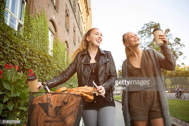 Young women on city street with bicycle.