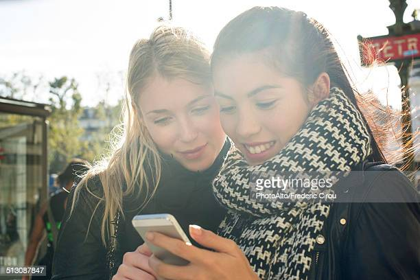 Young women outdoors looking at cell phone together