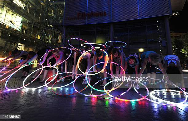 Young women perform with hula hoops during a flash mob as part of the hula hoop festival 'Hoopurbia' at Sonycenter at Potsdamer Platz in Berlin...