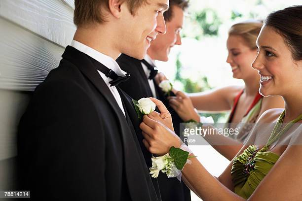 Young Women Pinning Boutonniere on Prom Dates