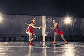 The two young women playing badminton over gym background. concept game in a pair