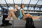 Young women posing on bench at train station