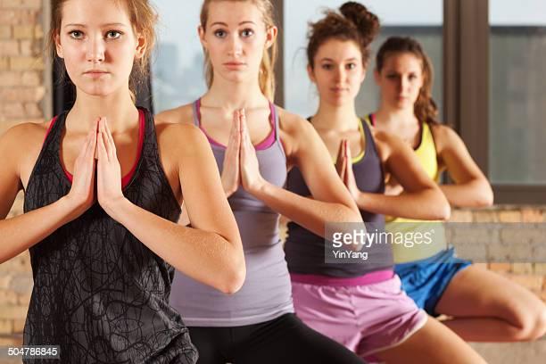 Jeune femme pratiquant la posture de l'arbre d'Yoga séance d'exercice en groupe