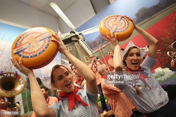 Young women promoting cheese from Holland hold up wheels of Dutch gouda as a brass band plays behind at the 2013 Gruene Woche agricultural trade fair...