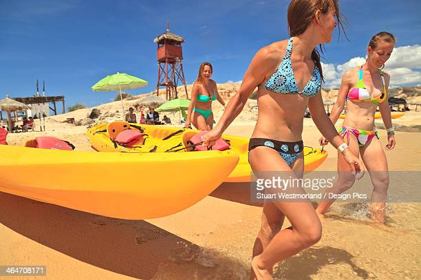 Young Women Pull A Boat Into The Water From The Beach At Cabo Pulmo