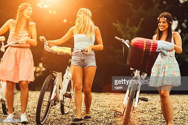 Young Women Pushing Bicycles On The Beach.