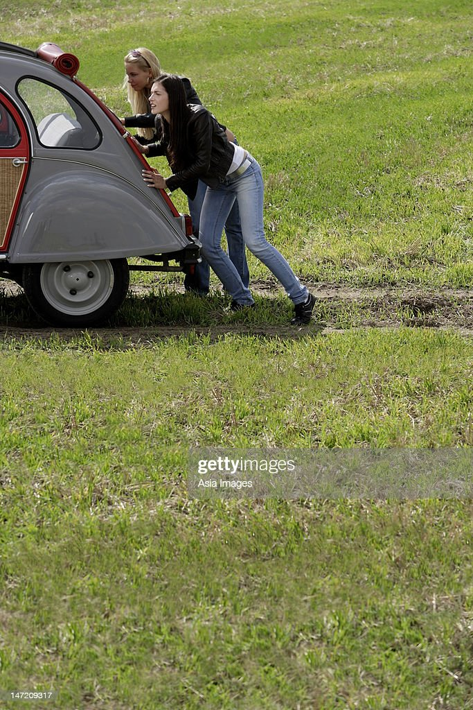 Broken Down Abandoned Stock Photos Broken Down Abandoned: Young Women Pushing Broken Down Car Stock Photo