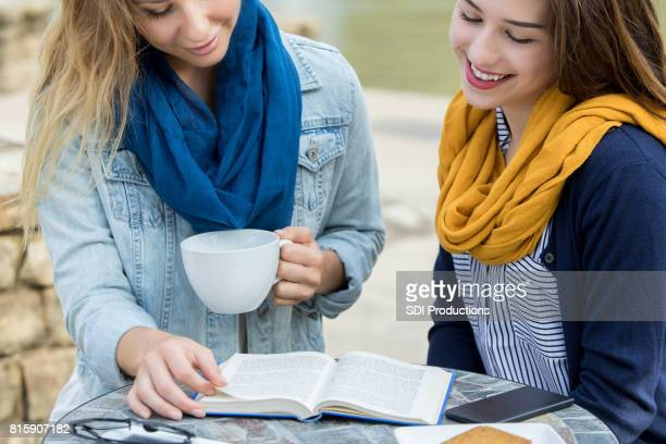 Young women read book together at outdoor cafe