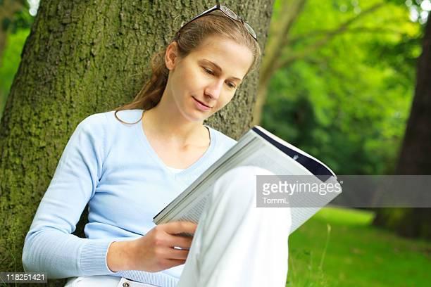Jeune femme lecture à l'extérieur sous un arbre