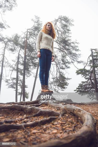 Young women redhead standing in woodland