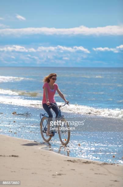 Young women riding a bike on the beach, Pas de Calais, Bitch.