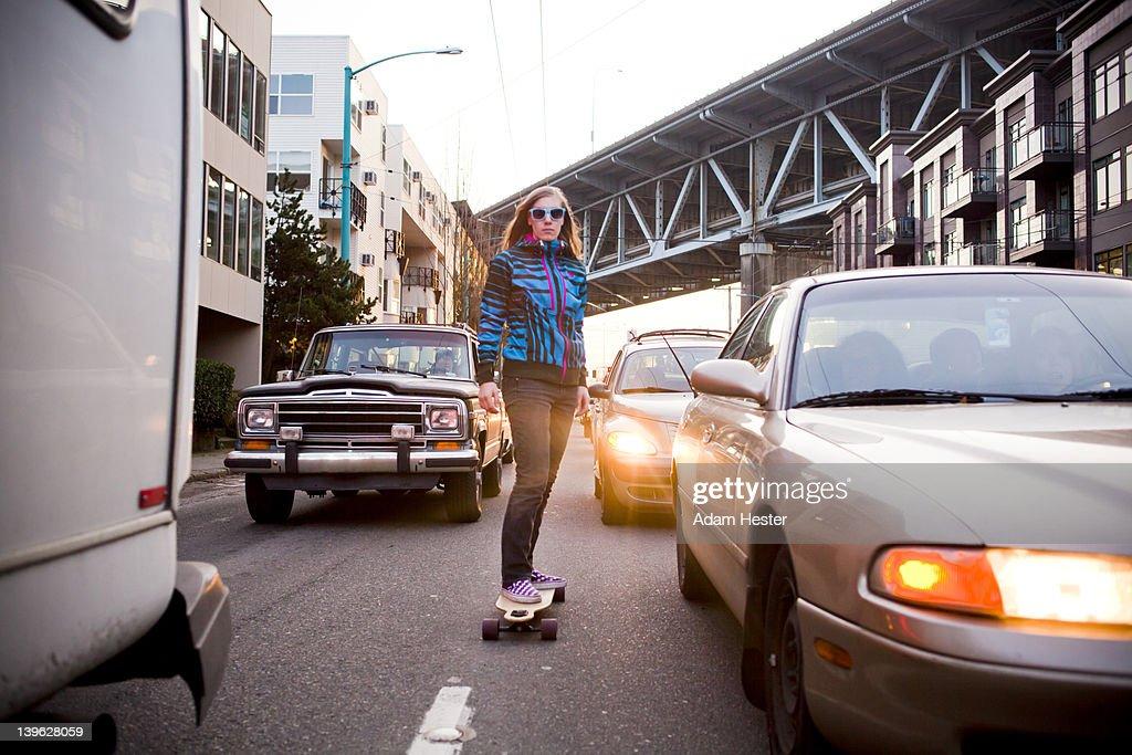 A young women riding a skateboard outside.