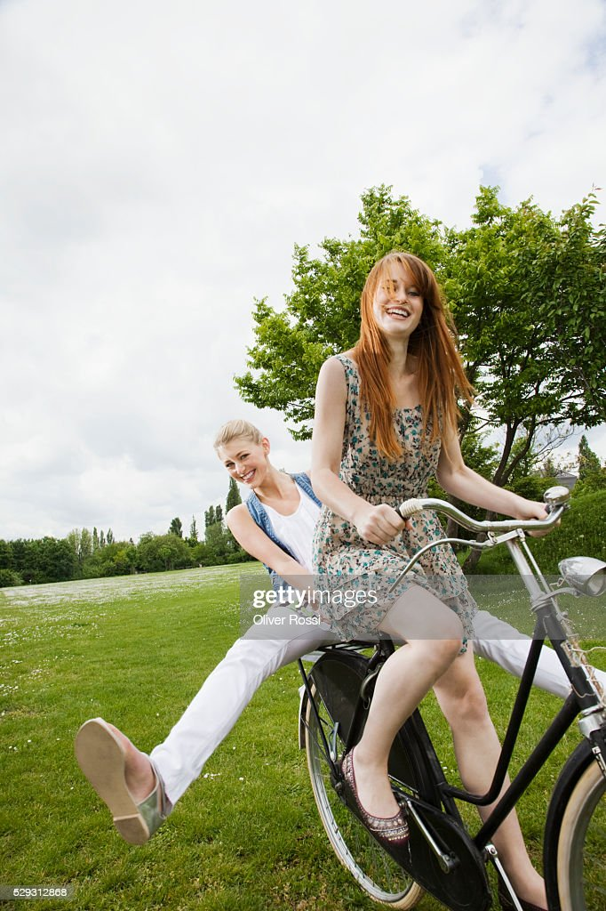 Young women riding bicycle in grass : Stockfoto
