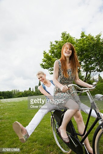 Young women riding bicycle in grass : Bildbanksbilder
