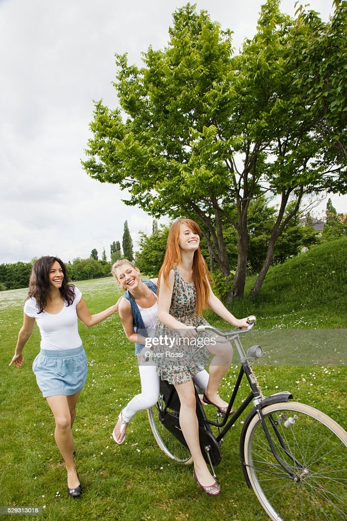 Young women riding bicycle in grass : Foto de stock