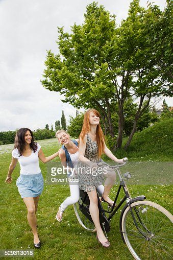 Young women riding bicycle in grass : ストックフォト