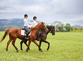 Two young women riding horses on green mountain meadow. Equestrian activity background