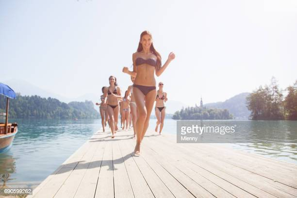 Young women running along jetty at Lake Bled Slovenia