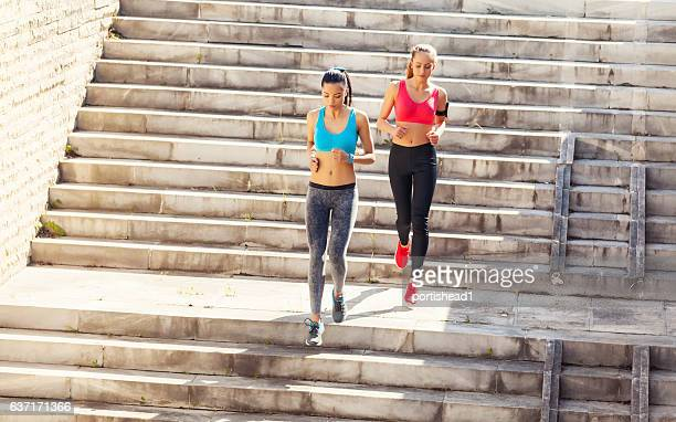Young women running down the stairs