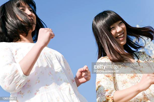 Young women running side by side, Japan
