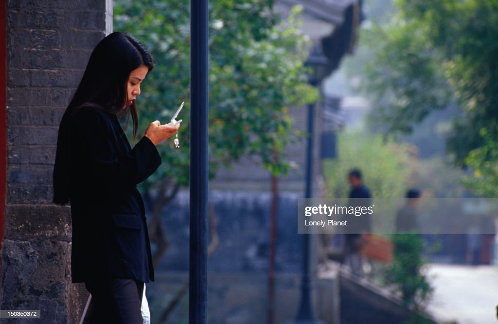 Young women sending SMS messages outside Baiyun Guan (White Cloud Temple). : Stock Photo