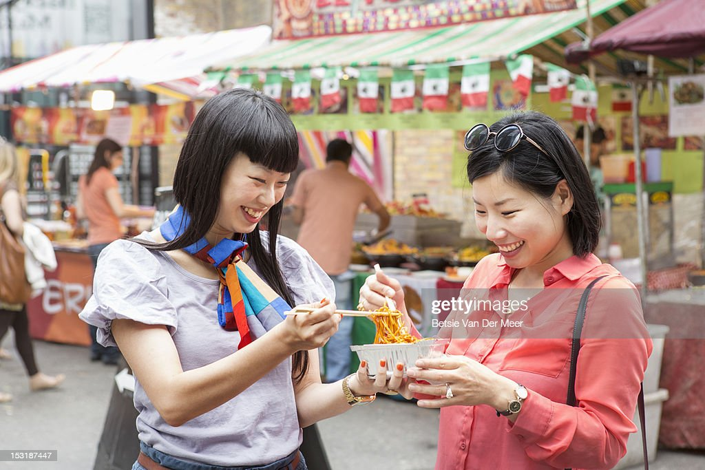 young women sharing noodle dish on market. : Stock Photo