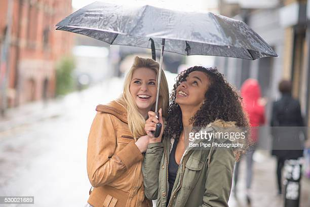 Young women sheltering under umbrella