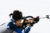 Young women shooting at biathlon competition