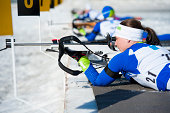 Young women shooting during biathlon competition