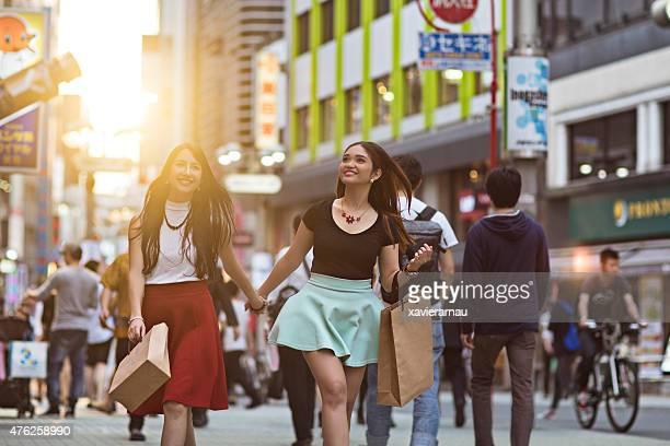 夕暮れの若い女性を東京のショッピング街