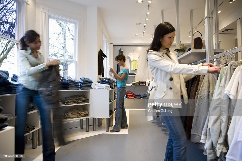 Young women shopping in clothing store : Stock Photo