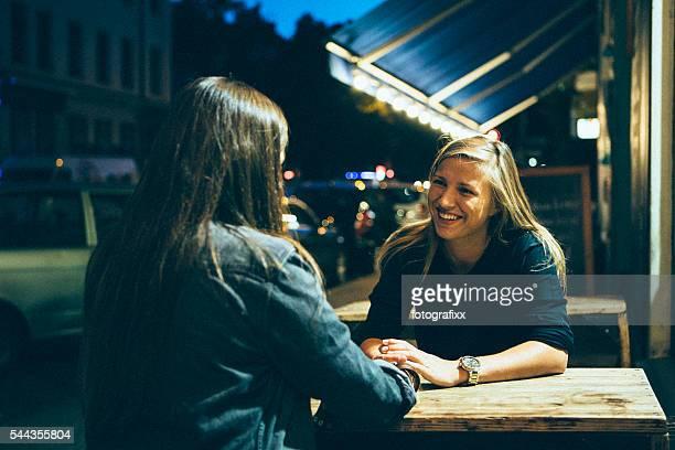 Jovem mulher sentada na rua café e falar, Berlim