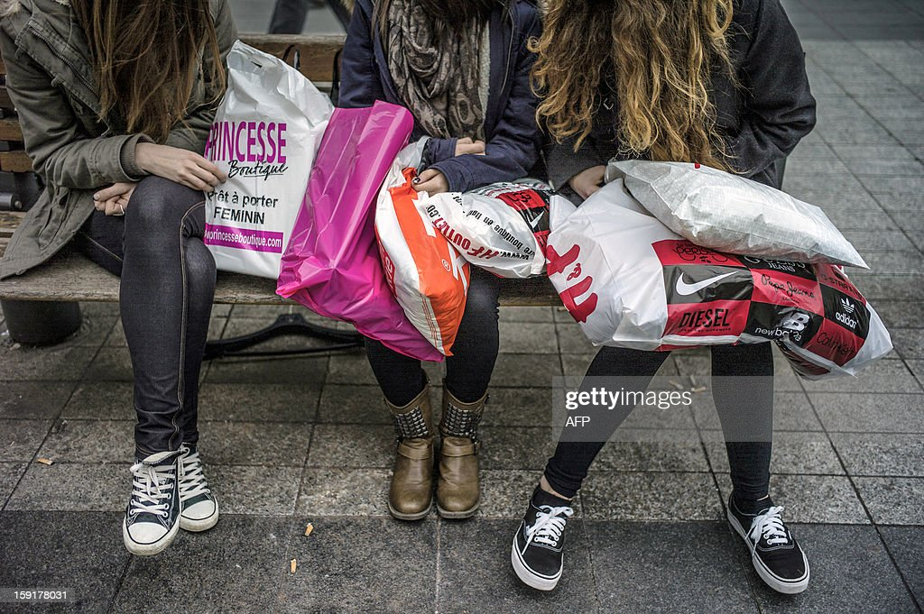 Young women sit on a public bench with shopping bags on the opening day of the winter sales on January 9, 2013 in Lyon, in central France. AFP PHOTO JEFF PACHOUD