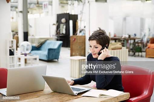 Young women sitting at desk, using laptop and mobile phone : ストックフォト