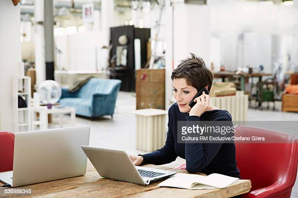 Young women sitting at desk, using laptop and mobile phone