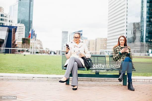 Junge Frau sitzt im park und mit Smartphone