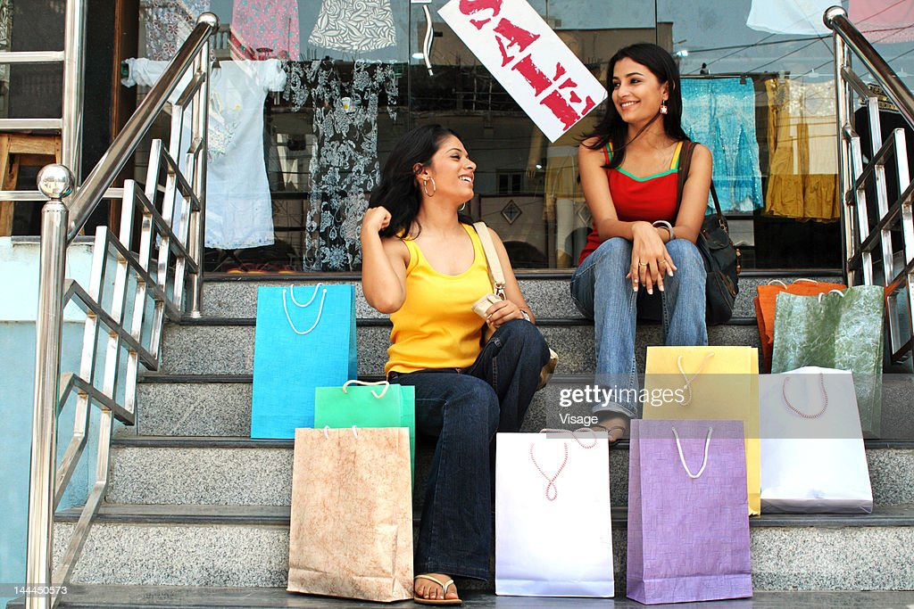 Young women sitting on the stairs with their shopping bags