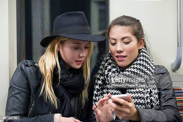 Young women sitting together on subway train, looking at smartphone