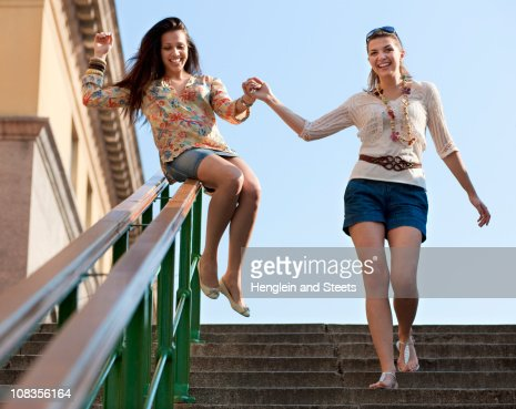 Young women sliding down railing