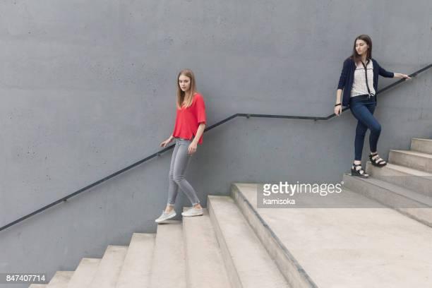 Jonge vrouwen permanent en bewegen op trappen door betonnen wand