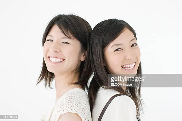 Young women standing back to back, smiling, studio shot