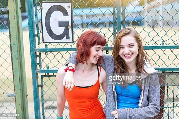 Young women standing beside sports ground, London, UK