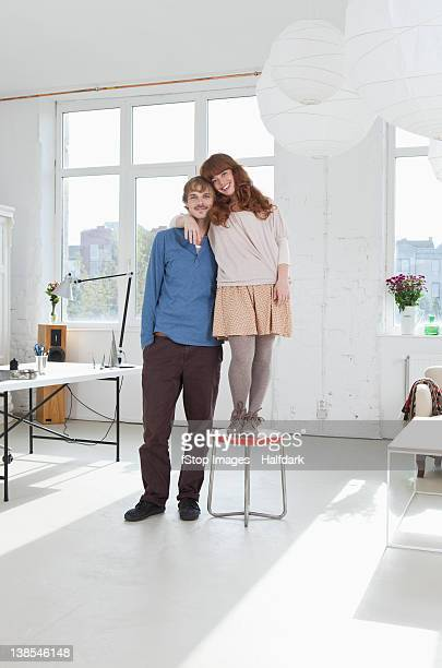 A young women standing on a stool next to her tall boyfriend
